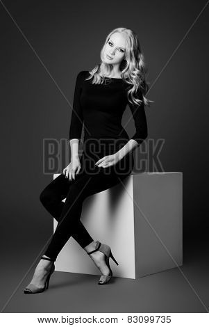 Art portrait of a beautiful slim young woman in black fitting clothing. Beauty, fashion. Body care.