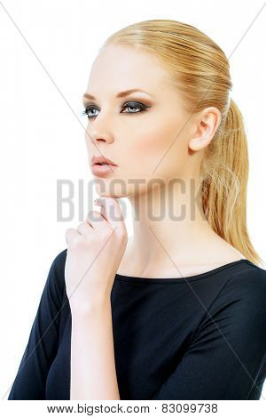Close-up portrait of a beautiful young woman with smoky eyes make-up wearing black fitting clothing. Beauty, fashion. Body care. Isolated over white.