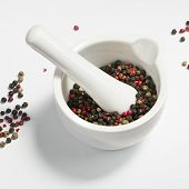 stock photo of peppercorns  - Red black green and white peppercorns in a white mortar - JPG