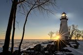 stock photo of marblehead  - The historic Marblehead Lighthouse in Northwest Ohio sits along the rocky shores of the frozen Lake Erie - JPG