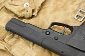 stock photo of handgun  - Handgun Lying Over a Camouflage Handbag - JPG