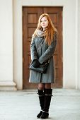 foto of redheaded  - Portrait of young beautiful redhead woman wearing coat and scarf posing outdoors with architectural background - JPG