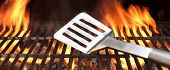 stock photo of barbecue grill  - Spatula on the Barbecue Charcoal Fire Grill with Black Background - JPG