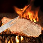 stock photo of flame-grilled  - Fork and Grilled Meat on the BBQ Grill - JPG