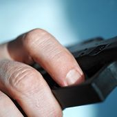 picture of gun shot  - Close up of a male hand pulling a gun trigger shot with shallow DOF - JPG