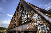 stock photo of graffiti  - Graffiti On Old Rusty Brown Metal Train Bridge - JPG