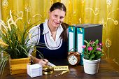 image of receptionist  - woman receptionist of hotel check in with plants - JPG