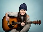 image of guitar  - young woman playing music on acoustic guitar - JPG