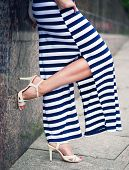 stock photo of slender legs  - Legs of woman with high heels dressed long striped dress outdoor - JPG