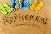 picture of sunny beach  - The word Retirement written on a sandy beach with scuba mask beach towel starfish and flip flops - JPG