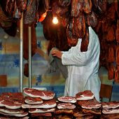 foto of pork belly  - Butcher at Pork Meat Fair with Stacks of Smoked Bacon and other Cured Pork Meat - JPG