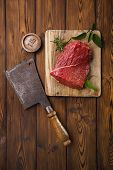 picture of meats  - raw beef meat fillet  on wooden  table with meat cleaver and 1lb iron weight - JPG