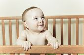 stock photo of teething baby  - Funny little baby with beautiful standing in a round white crib - JPG