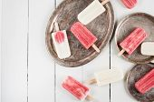 stock photo of popsicle  - Creamy and strawberry popsicles and vintage dishes on a white wooden board homemade food summer dessert - JPG