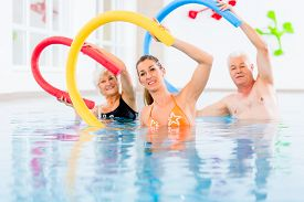 picture of noodles  - Group  or young and senior people in aquarobic fitness swimming pool exercising with  pool noodle - JPG