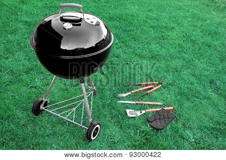 Bbq Grill Appliance On The Lawn With Tools And Glove