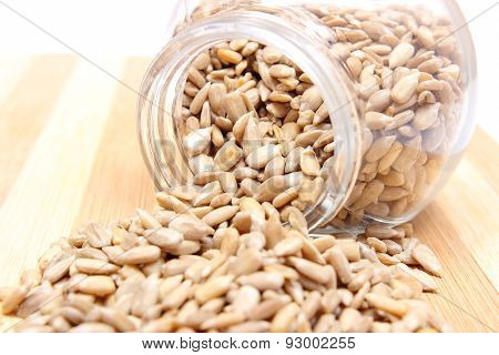 Heap Of Sunflower Seeds In Glass Jar On Wooden Cutting Board