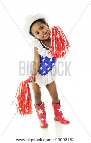 An adorable two year old in a star studded red, white and blue majorette outfit.  She wears a white cowgirl hat and holds two red and white pompoms.  On a white background.