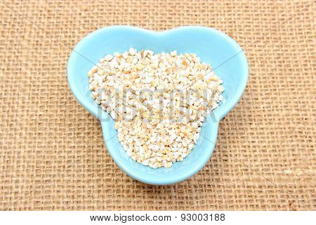 Barley Groats In Blue Bowl On Jute Canvas