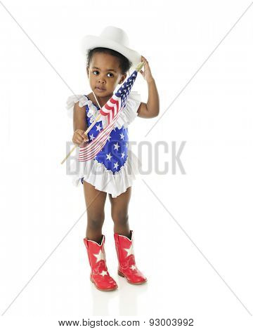 An adorable 2 year old in a star spangled majorette outfit adjusting her hat as she holds an American flag.  On a white background.