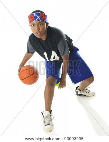 An African American tween basketball player actively dribbling his ball.  On a white background.