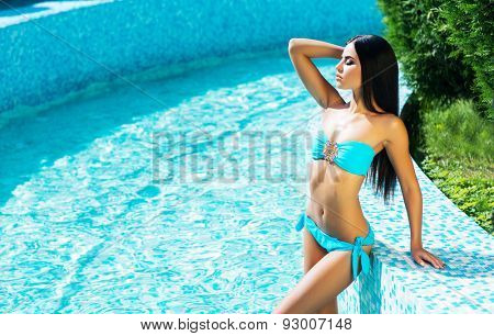 Beautiful, active and sporty girl relaxing in a pool at summer