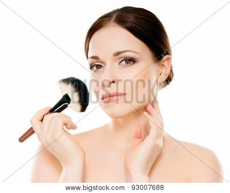 Beauty portrait of young, attractive, fresh, healthy and natural woman holding a makeup brush isolated on white