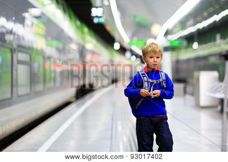 little boy with backpack travel by train