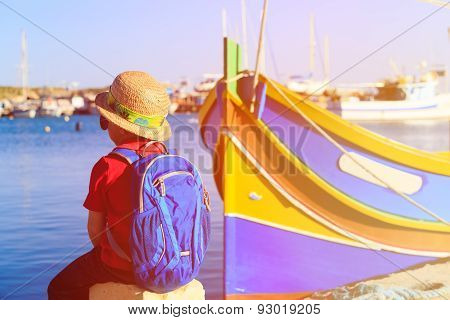 little boy looking at traditional boats in Malta