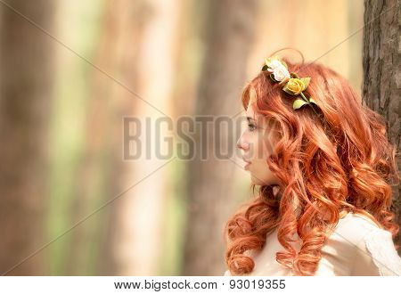 Side view portrait of beautiful redhead woman with gentle flower wreath in hair in the forest, fashion look, gorgeous hairstyle