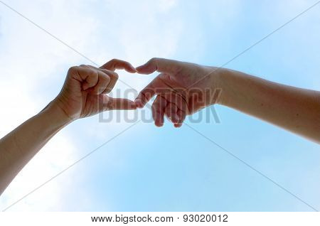 Two hands raising above blue sky in summer
