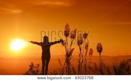 Sunset silhouette Young woman feeling to Freedom, silhouette happy woman arms up and feeling freedom