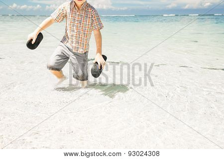 Happy young boy staying in the ocean water on beautiful beach wearing hat and sunglasses.
