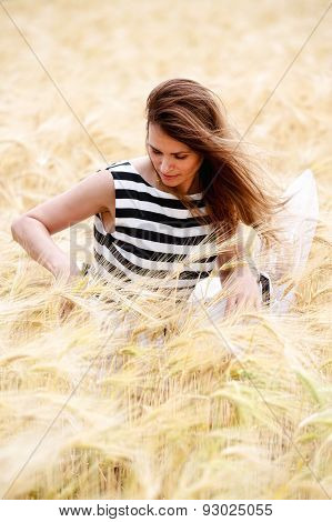 Gorgeous Girl Walking In The Field Of Long Grass And Dragging Her Hand Touching The Dry Grass While