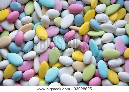 Background of sugared almonds color blue, rose, green, yellow, beige and white.