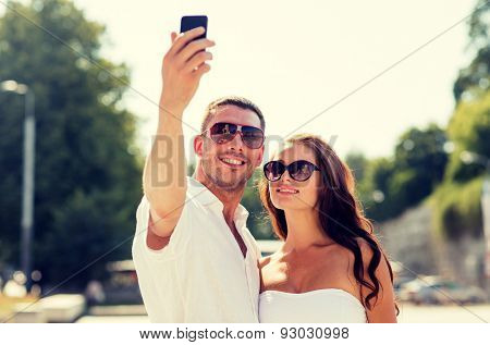 love, wedding, summer, dating and people concept - smiling couple wearing sunglasses making selfie with smartphone in park