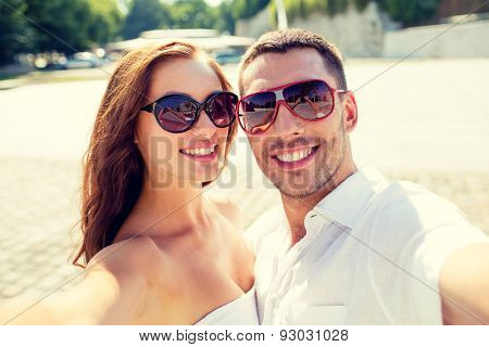 love, wedding, summer, dating and people concept - smiling couple wearing sunglasses making selfie in city
