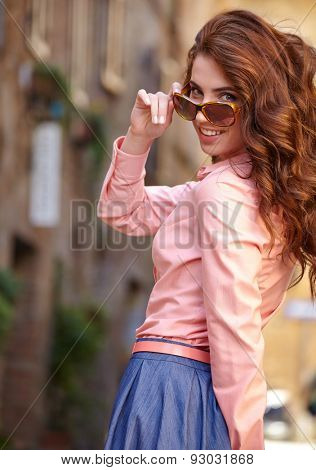 beautiful woman in summer dress walking and running joyful and cheerful smiling in Tuscany, Italy.