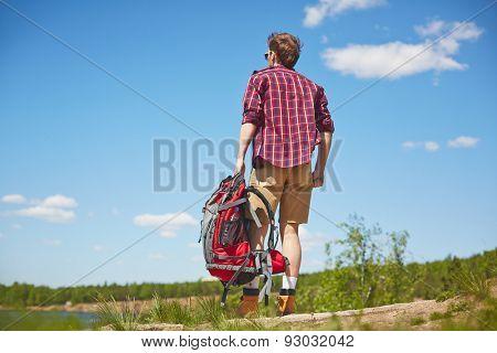 Young traveler with rucksack enjoying trip