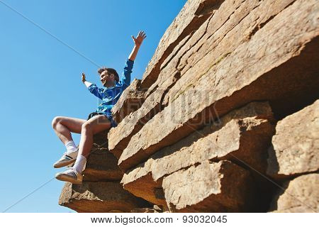 Happy man with raised arms sitting on top of rock