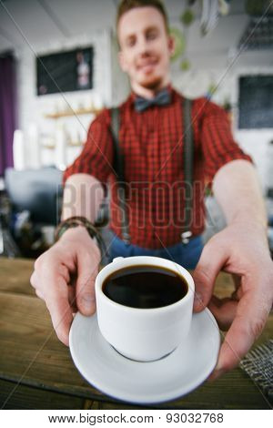 Barista giving cup of black coffee