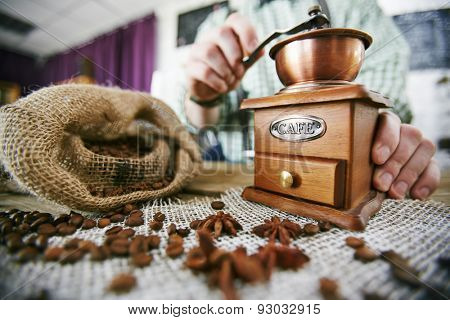 Barista tampering coffee beans at workplace