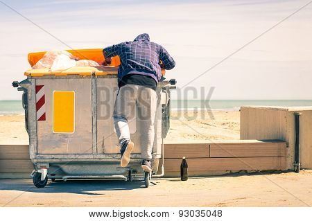 Young Tramp Rummaging In Trash Container Looking For Food And Reusable Goods - Poverty Concept