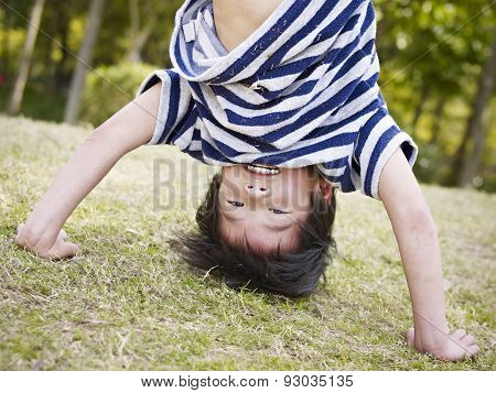 Asian Child Standing On Hands Outdoors