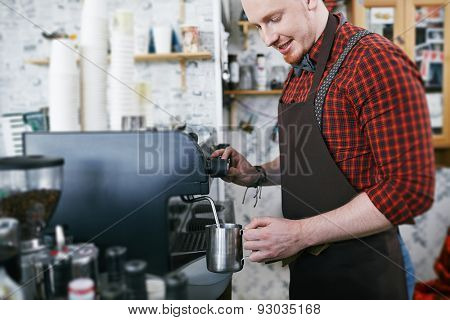 Young man in apron using coffee machine