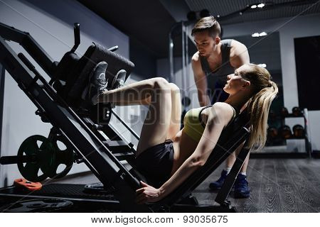 Active woman doing exercise for legs on special equipment with trainer near by