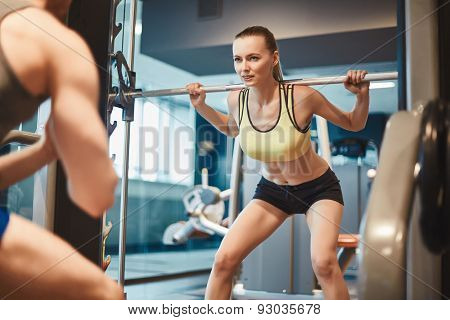 Pretty woman with weight looking at her trainer in gym