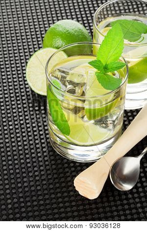 Mojito cocktail and ingredients on black rubber mat