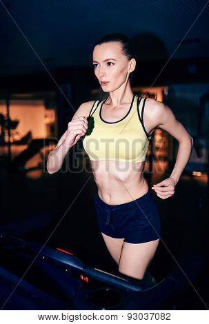 Fit girl in activewear running on treadmill