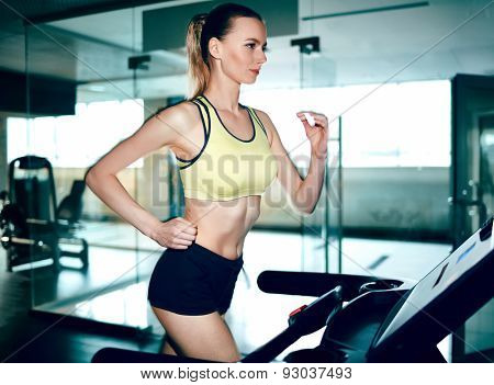 Active female running on treadmill in gym poster
